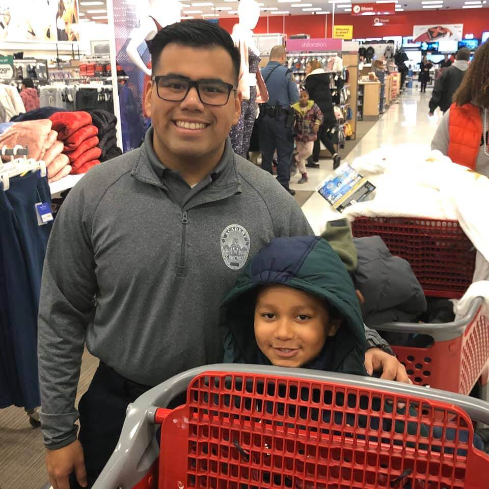 Police officer and young boyshopping at Target, smiling at the camera.