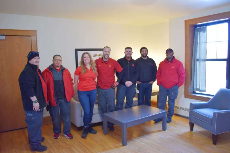 CORT furniture volunteer team standing in the living room of the apartment unit that they painted and furnished