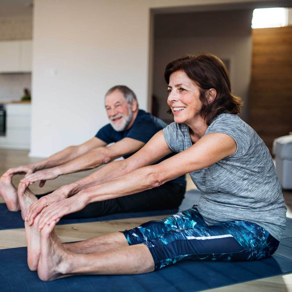 mature white couple in sitting forward fold pose at home workout