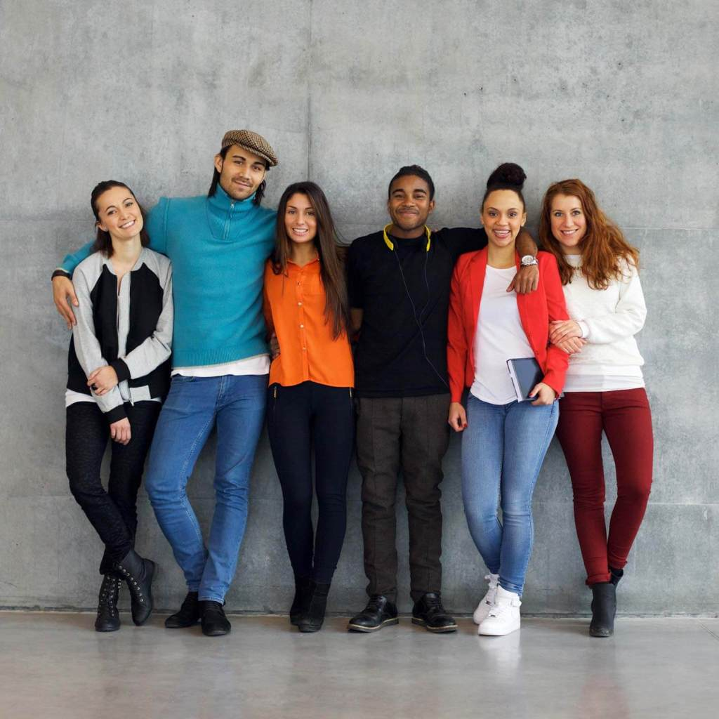 group of multiethnic teens hugging each other while leaning against wall
