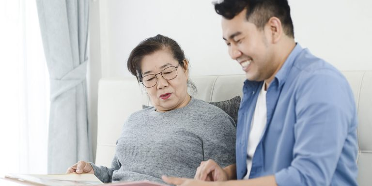 Asian man and his mother looking at photo album together