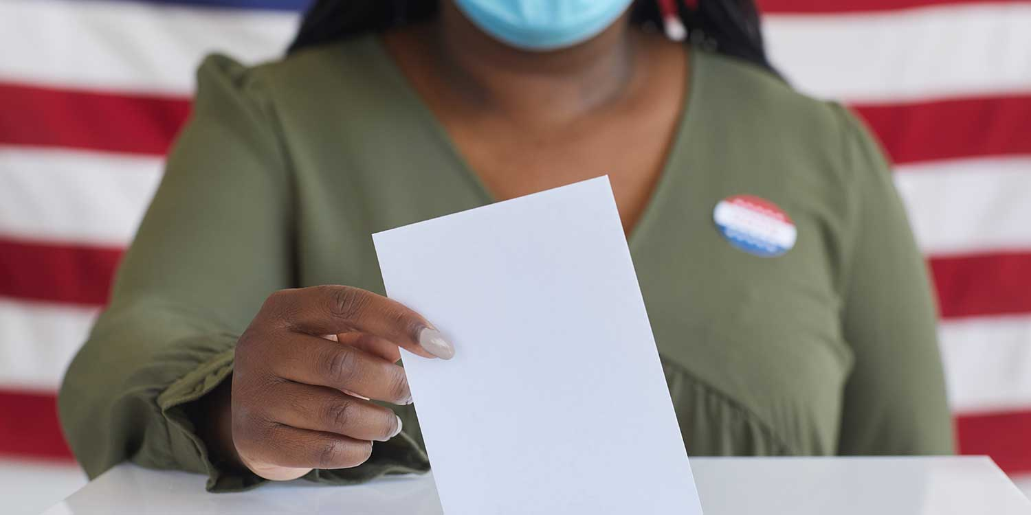 Close up of African-American woman wearing mask putting vote bulletin in ballot box and looking at camera while standing against American flag on election day