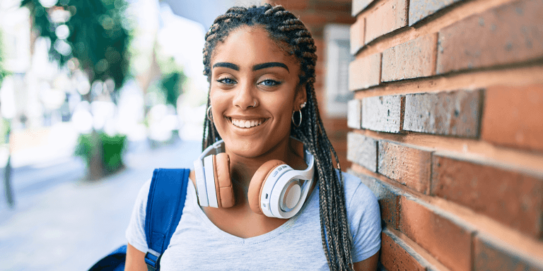 Young african american student woman smiling happy leaning on the wall at the university campus
