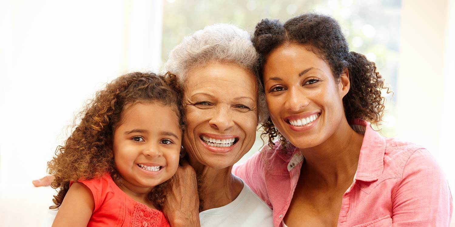 African American Mother,daughter and granddaughter at home smiling at the camera