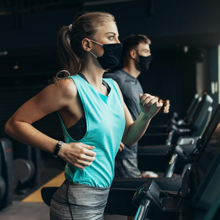 Young fit woman and man running on treadmill in modern fitness gym. They keeping distance and wearing protective face masks.