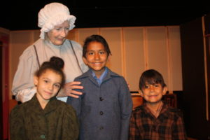 "Sue Kelly as Anne, the nurse, keeps watch over her charges, from left, Lea Maya and Emmy, Nicholas Perez as Ivar and Christopher Perez as Bob, in the Theatre 29 production of ""A Doll's House."""