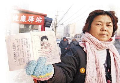 Guo Chuping enseña al diario pequinés Jinghua Shibao los documentos que muestran que recibe las ayudas del gobierno por desempleo.