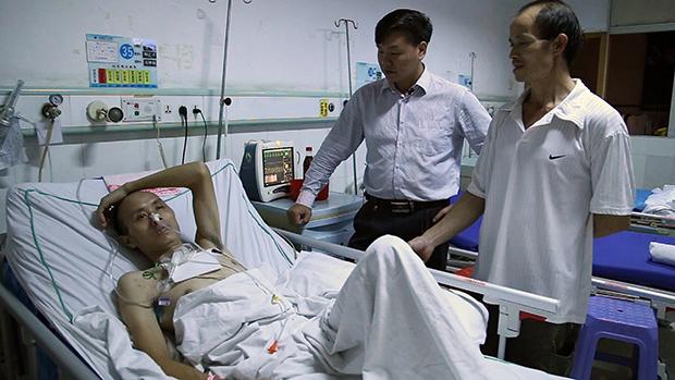 Zhang Zhiru, de pie, junto a un obrero hospitalizado, en una de las escenas del documental.