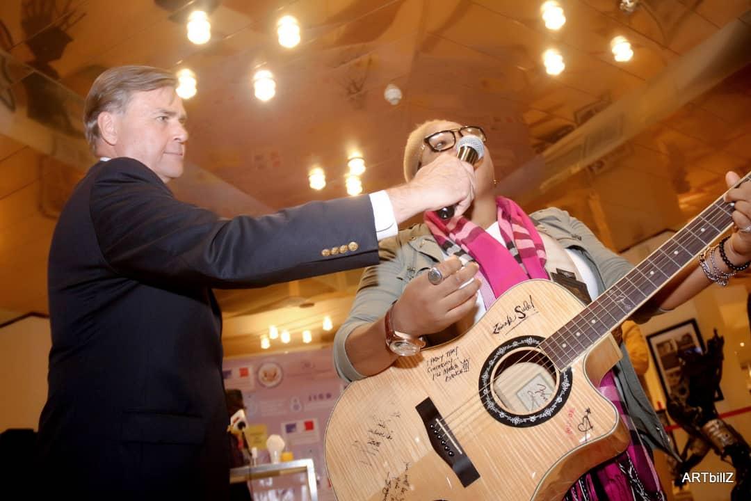 us ambassodor holds mic for Zainab Sule
