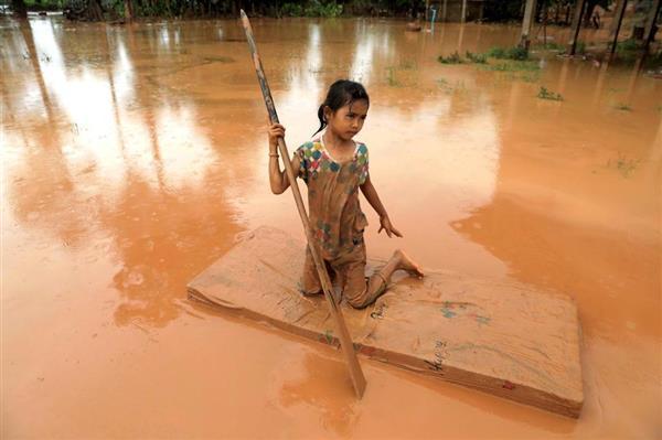 「泥地獄」と化したラオス。マットレスで泥水の上を移動する少女の姿もあった(ロイター)