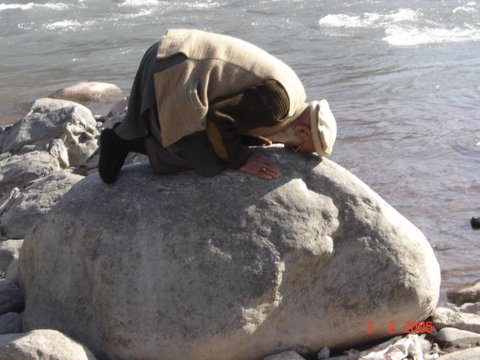 Elderly Muslim man praying on a rock