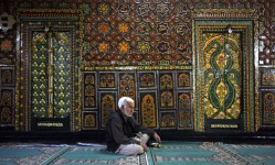 Kashmiri man prays in a sufi shrine