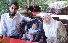 Muslim couple and baby, at a restaurant