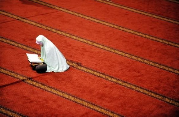 Muslim woman reading Quran.