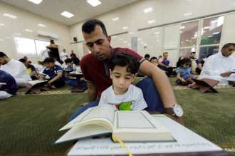 A boy in Qatif, Saudi Arabia reads Quran with his father's guidance.