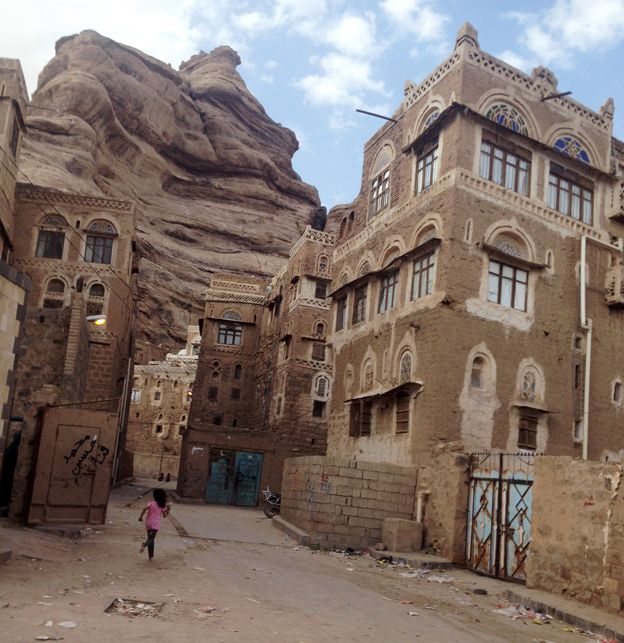 Yemeni child plays in Sawan, in front of traditional Yemeni homes