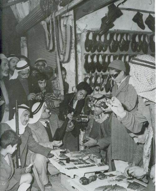 """. חפים מפשע או """" פורעים"""" חנות נעליים שבה נמכר נשק לכל דורש בשוק, ערב מלחמת הקוממיות. (ארכיון יעקב אלעזר)."""