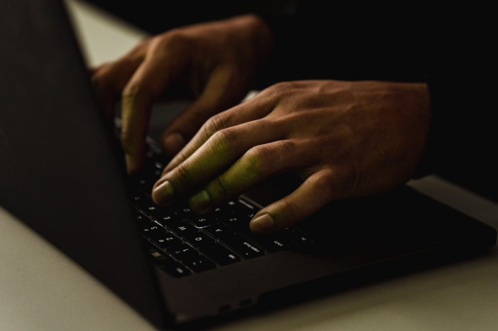 crop unrecognizable person typing on laptop keyboard