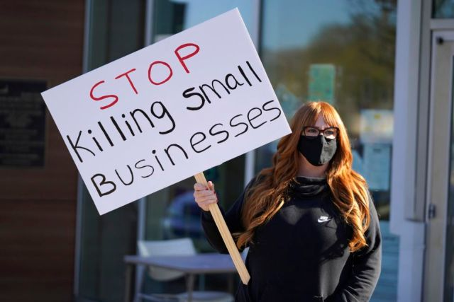 Lisa Kreyer holds up a sign during a protest by hair salon owners and workers against the latest lockdown orders outside the offices of Marin County Health Officer Dr. Matt Willis Thursday, Dec. 10, 2020, in San Rafael, Calif. California health officials are urging the state's residents to stay home as much as possible due to a coronavirus surge taxing the state's hospitals. But the most recent stay-at-home order allows some businesses to remain open, frustrating shuttered business owners who say officials keep sending mixed messages. (AP Photo/Eric Risberg)