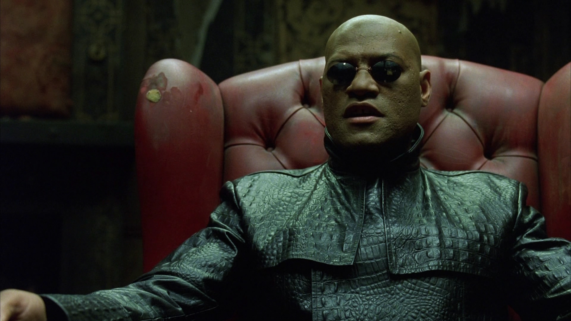"""Morpheus (from """"The Matrix"""") seated in a leather chair in a dark room."""