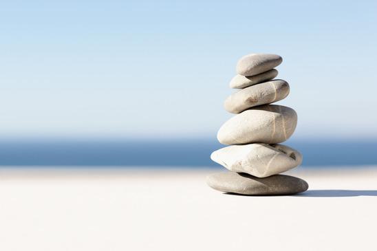 5 steentjes opeengestapeld op een strand