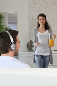 Woman carrying glass of juice to man wearing headphones
