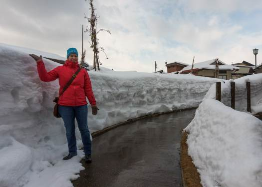 Standing in front of large Snowbanks at Nozawa Onsen