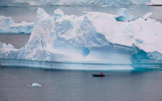 Zodiac cruising by a massive iceberg in Antarctica