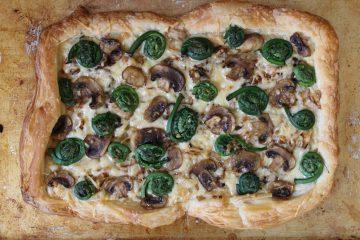 Delicious Fiddlehead, Mushroom, Caramelized Onion & Gruyere Tart makes for a tasty springtime meal.