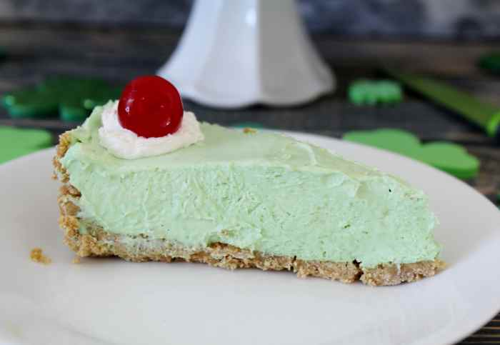 Baileys Shamrock Shake Cheesecake - a boozy twist on the St Patrick's Day favourite! This minty green frozen no bake cheesecake is the BEST dessert recipe for your St Patty's Day celebrations. You really will be feeling lucky when you enjoy this treat!