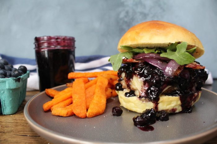 Blueberry Brie Bacon Burger on a plate with sweet potato fries.