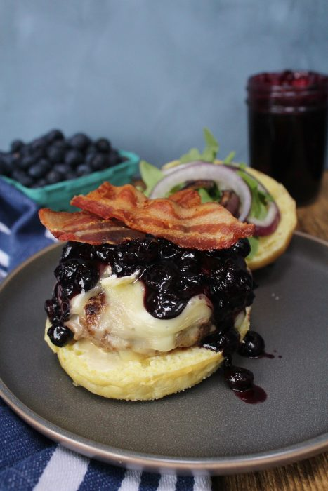 Blueberry Brie Bacon Burger with the top bun off, showcasing the burger pattie, barbecue sauce, and bacon.