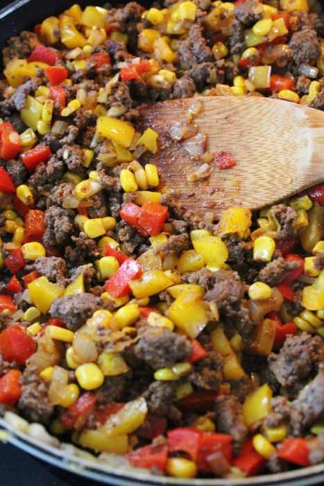 A mixture of ground beef, diced onions, diced bell peppers, and corn.