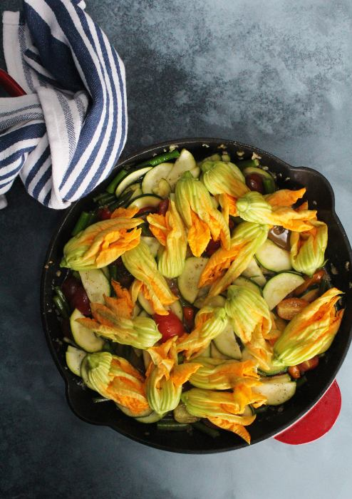 A cast iron skillet with zucchini, garlic scapes, cherry tomatoes and squash blossoms.