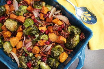 Maple Roasted Brussels Sprouts and Sweet Potatoes with Cranberries and Pecans - Brussels sprout and sweet potatoes are roasted together with cranberries, pecans, and a maple balsamic glaze, getting crispy and carmelized.  This makes for a wonderful Thanksgiving side dish or for other holidays and celebrations throughout the fall and winter!