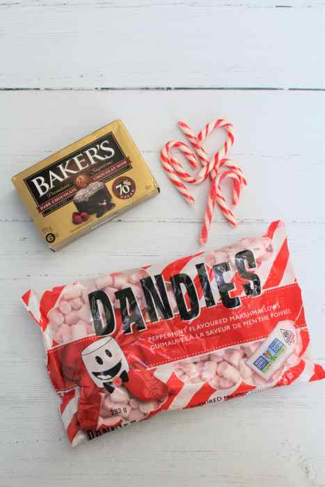 Baker dark chocolate in the top left, miniature candy canes to the right of it, and a package of Dandies peppermint marshmallows below on a white wood backdrop