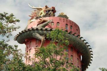 La torre di un tempio buddista avvolto dalle spire di un drago