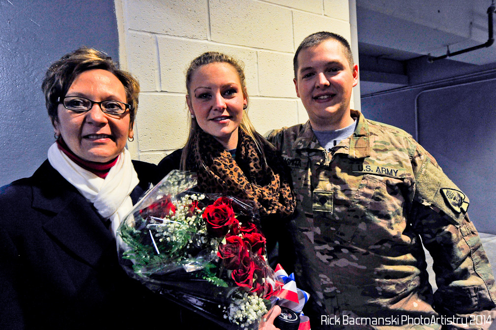"Ziff Law's Annette Viselli Thorne, left, joins Army Spc. Albert ""Joey"" Daghita and his wife Brittany after the Veterans of the Game surprise Saturday at First Arena."