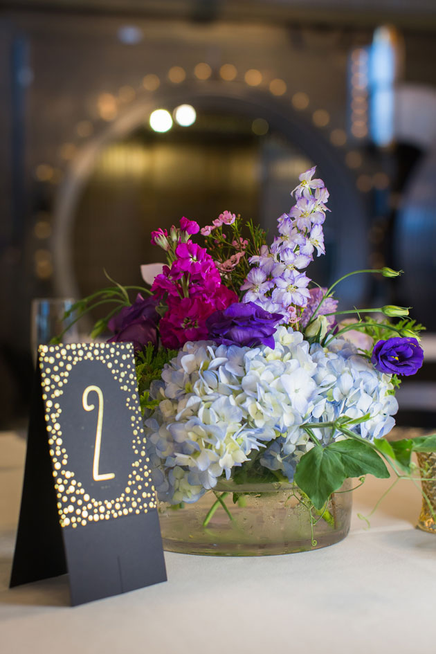 embellished gold table number and floral centerpiece