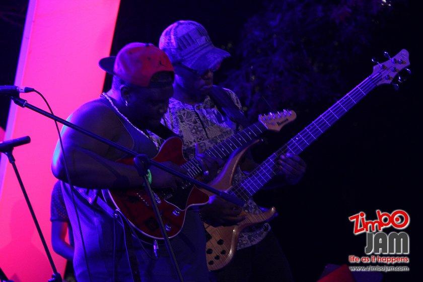 Tinos on the bass guitar (in cap) alongside guitar Sangoma.