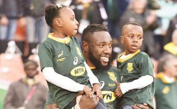A GOLDEN BEAST . . . Zimbabwe-born Springboks star Tendai ''Beast'' Mtawarira holds his two kids as he walks into the stadium in Bloemfontein, South Africa, last Saturday when he marked 100 Test caps for his adopted country