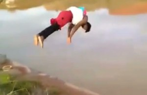 Video of a woman jumping in a dam whilst carrying her baby on her back