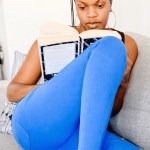 A woman wearing blue pants and a headrap reading a book