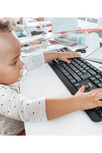 a baby with her hands on a keyboard