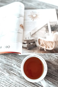 a cup with tea and an open magazine
