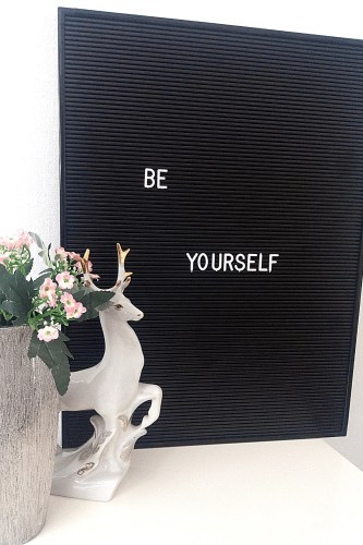 be yourself letters and a black letter board, and pink flowers, silver vase