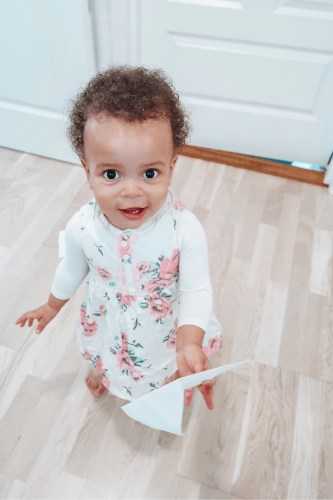 baby holding a white envelope