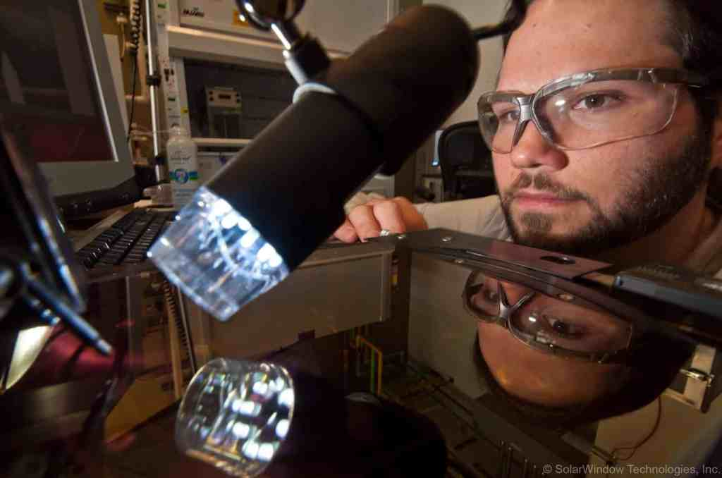 Dr.Scott Hammond testing the coating under artificial light. Image credits SolarWindow.
