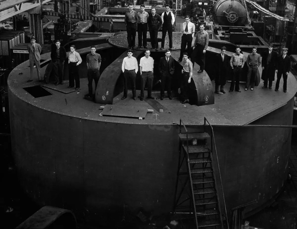 Engineering students pose for a picture atop one of the 2 million-pound hydroelectric generators for the dam at the General Electric factory in Schenectady, New York (1935).