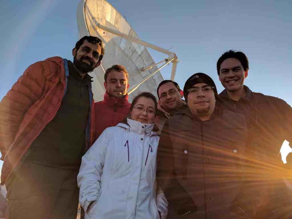 EHT team posing for a picture with the massive LMT radio dish in the background. Credit: UMassAmherst.